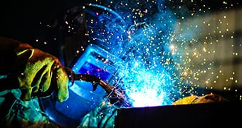 Operator with safety mask welding parts with blue arc weld and sparks