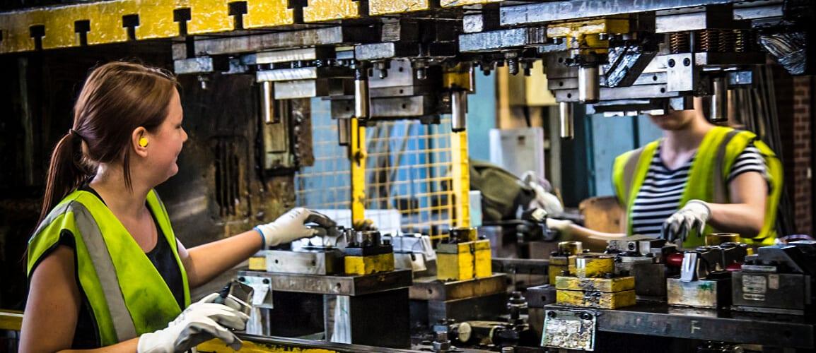 Two women at a manual press making metal parts for Honda